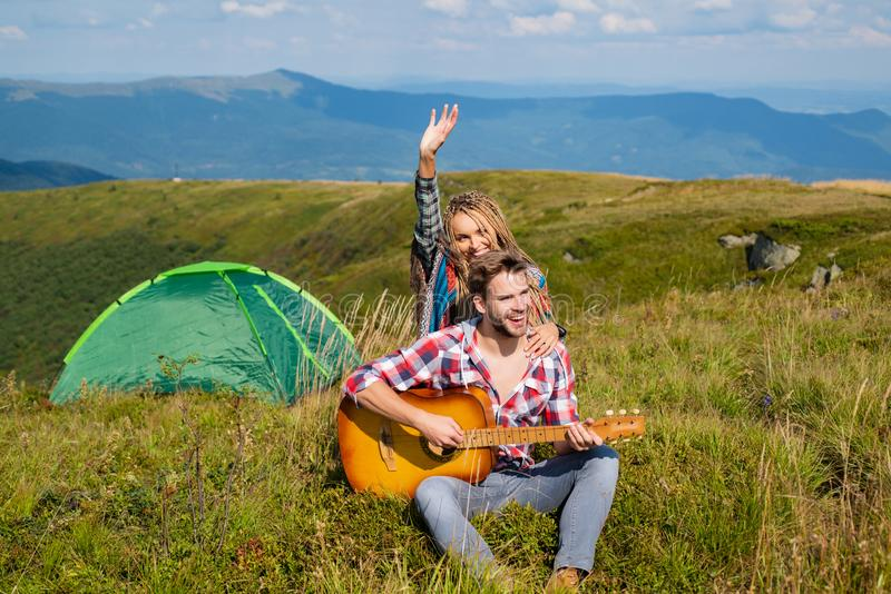 Travel couple enjoying wanderlast view, woman with arm up in excitement at mountain background. Happy family on vacation stock images