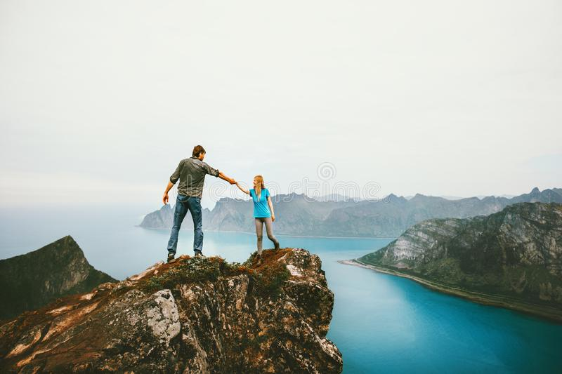 Travel couple hands holding together on cliff edge in Norway. Men and women family healthy lifestyle summer vacations outdoor friends happy emotions royalty free stock image