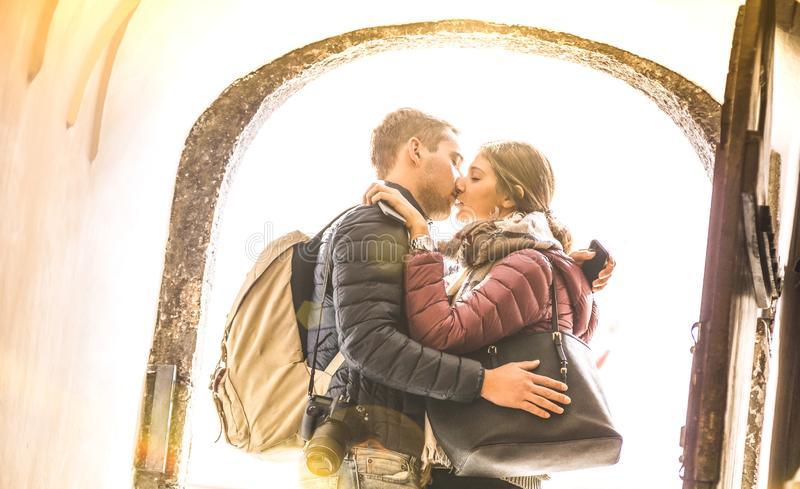 Travel couple in love kissing outdoors at city tour excursion - Young happy tourists enjoying romantic moment at sunset stock image