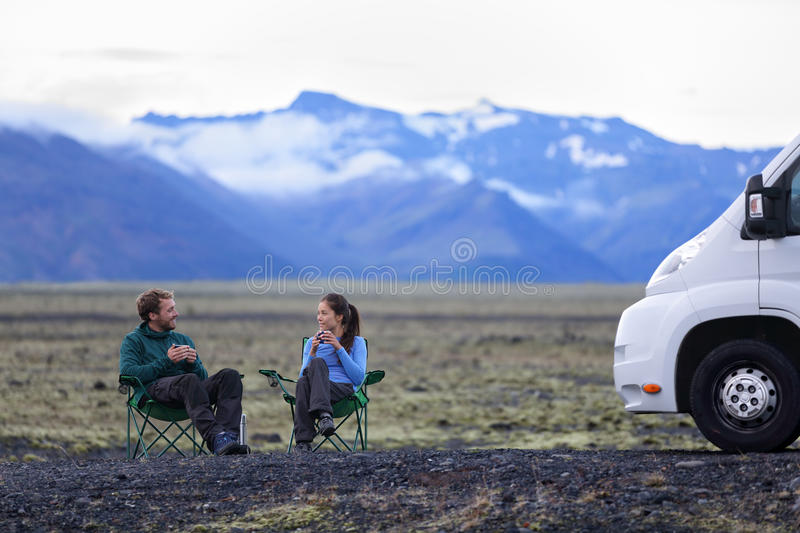 Travel couple by mobile motor home RV campervan. People sitting in chairs relaxing camping and enjoying traveling on Iceland in recreational vehicle. Young royalty free stock photo
