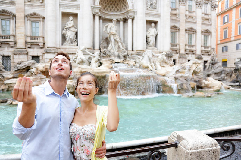 Travel couple trowing coin at Trevi Fountain, Rome. Italy for good luck. Happy young couple smiling traveling together on romantic travel vacation holiday in stock photos