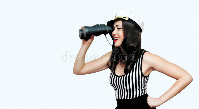 Travel, cruise, people concept - pretty smiling woman brunette sailor looking through binoculars, pin-up style. Over empty copy space white background royalty free stock photography