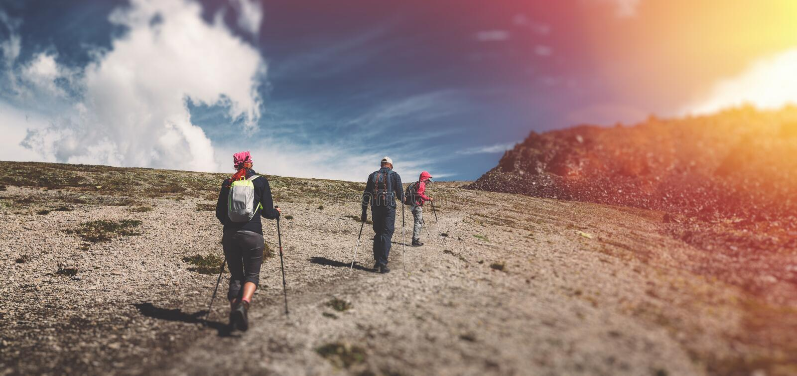 Travel Destination Experience Lifestyle Concept concept. Team of travelers with backpacks and trekking sticks climbs the mountain royalty free stock photos