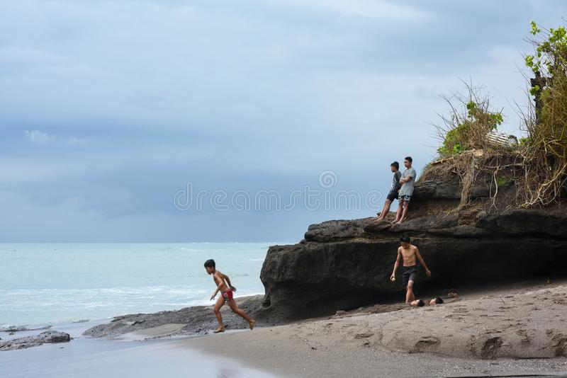Travel destination. Happy Balinese boys laughing and playing on the beach.Canggu, Bali, Indonesia, 24 September 2016 royalty free stock photos