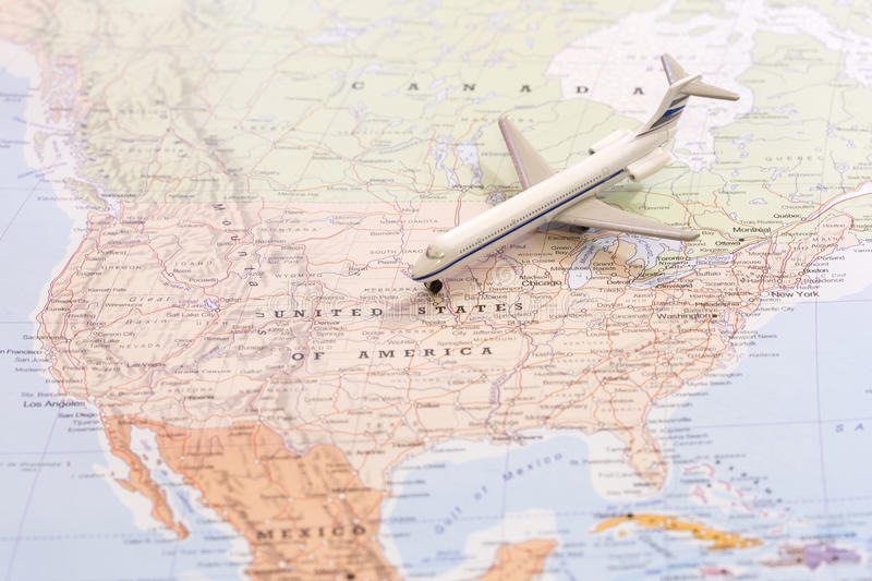 Travel destination USA. Passenger airplane miniature on a map. Miniature of a passenger airplane flying on the map of United States of America from north east stock photography