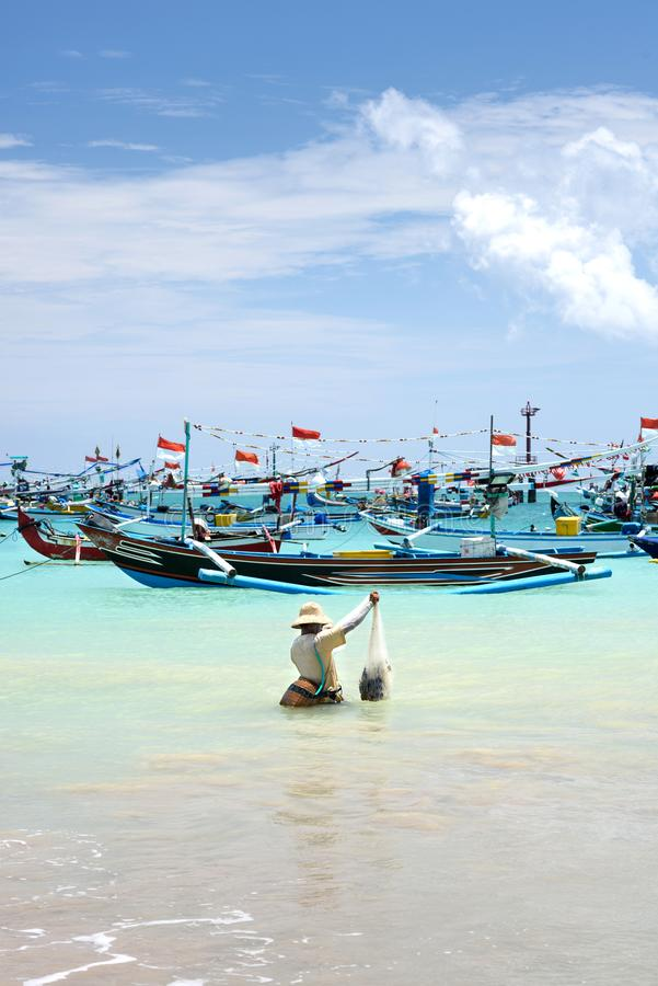 Travel destinations, island culture. Fisherman, catching fish in the ocean, traditional balinese boats, exotic Bali, stock photography