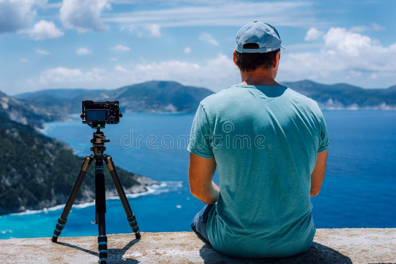 Travel Europe summer holiday in Greece. Happy man photographer enjoying cloudscape, coastline and Mediterranean sea royalty free stock images
