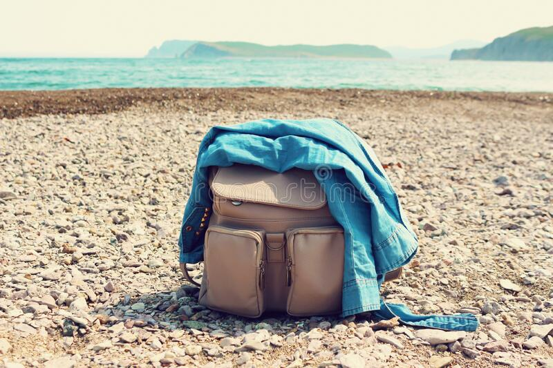 Travel female backpack with jeans shirt  on a sea coast. Fashion vacation concept stock photos