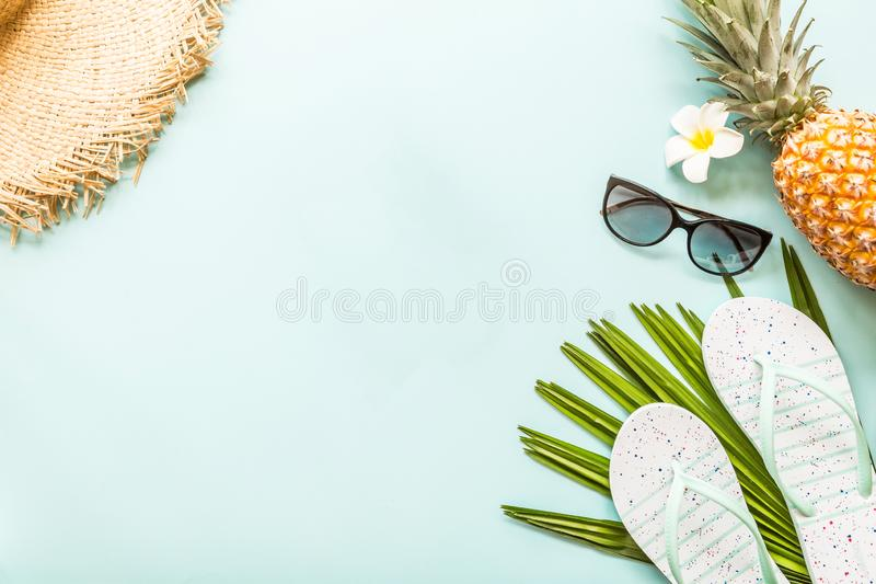 Travel flat lay items: fresh pineapple, straw hat, flower, sunglasses, beach slippers and palm leaf. Place for text. Top view stock photo
