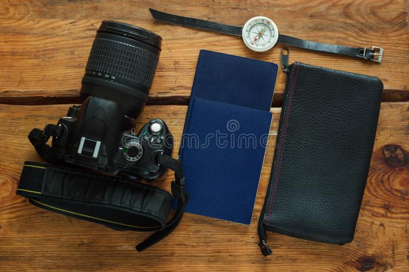 Travel flatlay on brown wooden background with camera, international passports, wallet and compass stock photos