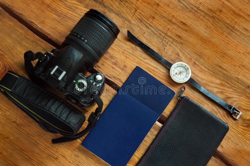 Travel flatlay on brown wooden background with camera, international passports, wallet and compass. Top view of traveler items, lifestyle accessories. Vacation stock photography