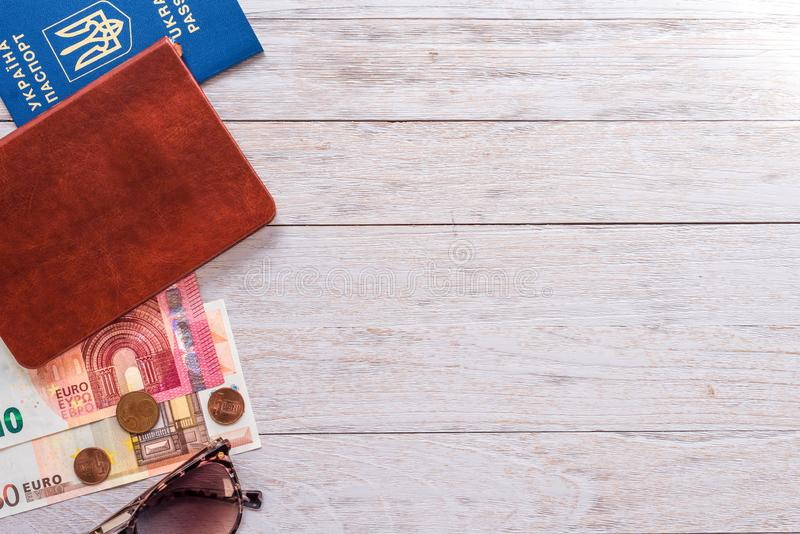 Travel flatlay: passport, pocketbook, money and sunglasses on white boards stock photography