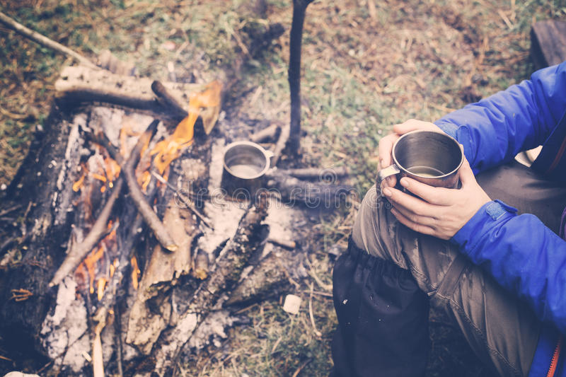 Travel girl drinking from a mug. Camping hiking lifestyle. royalty free stock photography