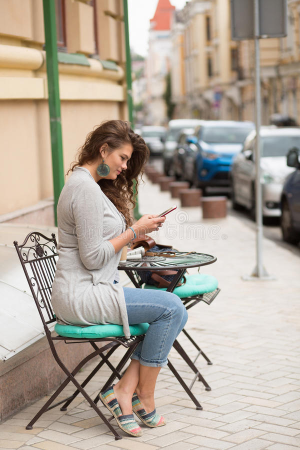 Travel girl siting at small coffee table in the street of the city. stock photo
