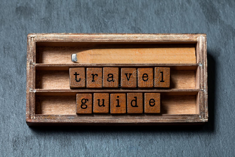 Travel guide concept. Vintage box, wooden cubes phrase with old style letters, retro pencil. Gray stone textured. Background. Close-up, up view, soft focus stock photo
