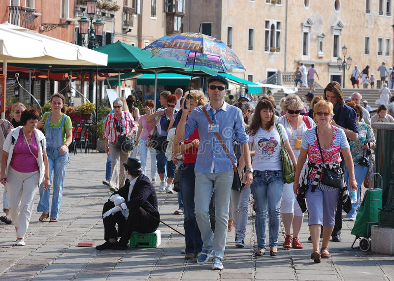Travel guide and tourists in Venice/Venezia. Travel guide and tourists arriving in Venice/Venezia - Italy and walking towards Piazza San Marco stock photo