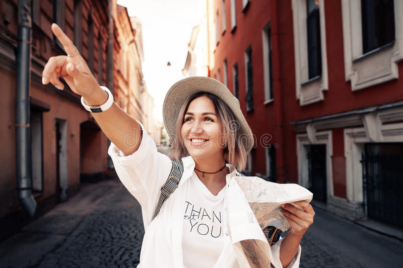 Travel guide. Young female traveler with backpack and with map on the street. Travel concept royalty free stock photos