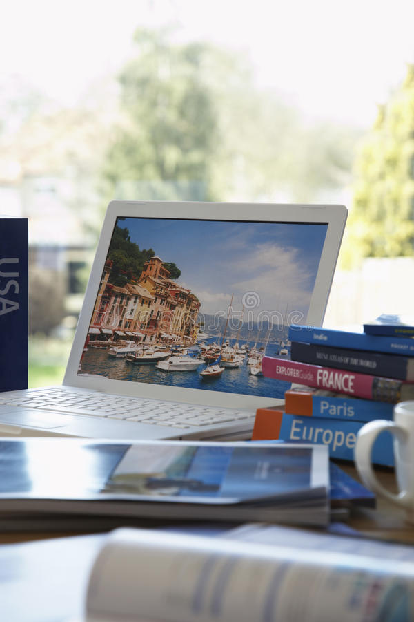 Travel guides next to laptop on table royalty free stock photography