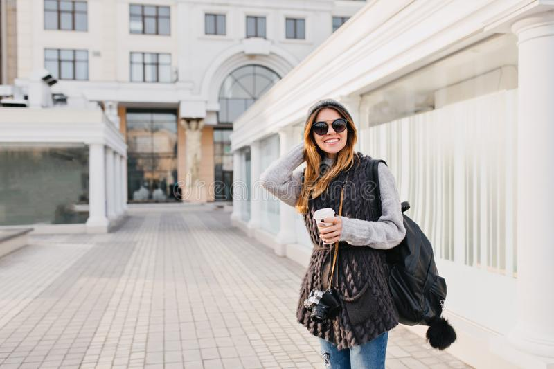 Travel happy time in modern city centre of yoyful pretty young woman in sunglasses, warm winter woolen sweater, knitted stock photo