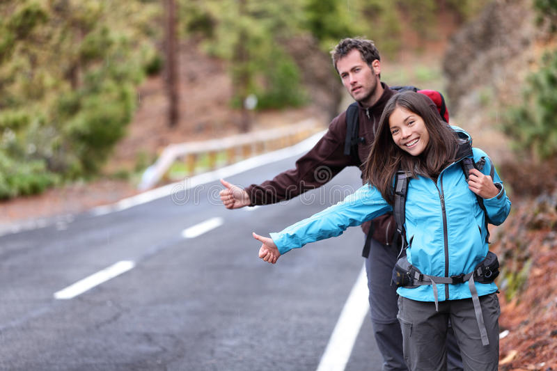 Travel hikers couple hitchhiking on road trip royalty free stock photo