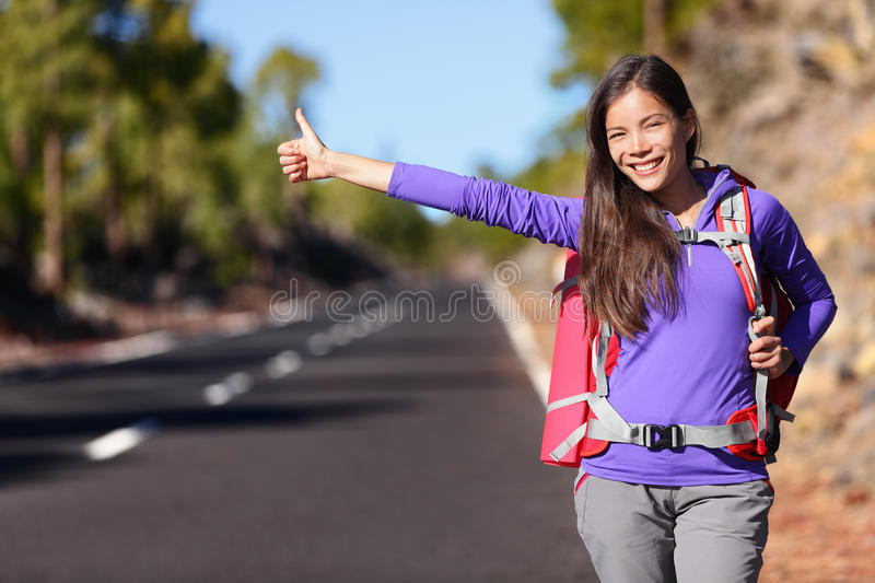 Travel hitchhiker woman backpacking hitchhiking. Thumbing happy walking on road side during holiday travel. Beautiful outdoors woman model. Mixed race Asian royalty free stock image