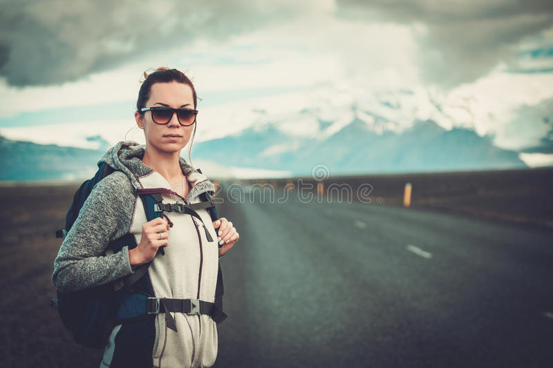 Travel hitchhiker woman walking on a road. Travel hitchhiker woman walking on road during holiday travel stock images