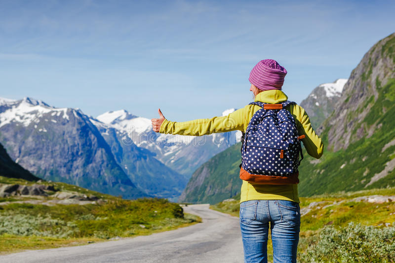 Travel hitchhiker woman walking on road during holiday travel. Hitchhiking tourism concept. Travel hitchhiker woman walking on road during holiday travel royalty free stock image