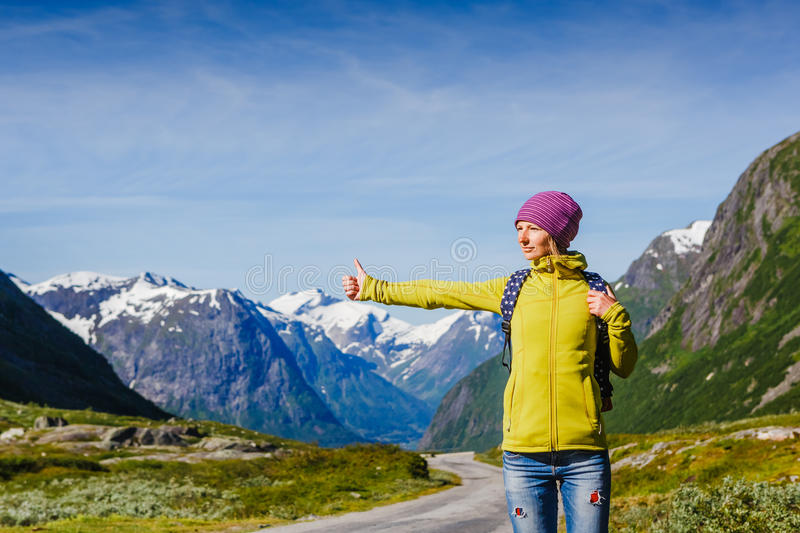 Travel hitchhiker woman walking on road during holiday travel. Hitchhiking tourism concept. Travel hitchhiker woman walking on road during holiday travel stock photography