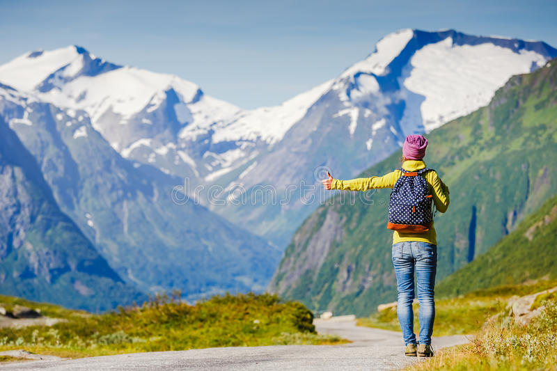 Travel hitchhiker woman walking on road during holiday travel. Hitchhiking tourism concept. Travel hitchhiker woman walking on road during holiday travel stock photo