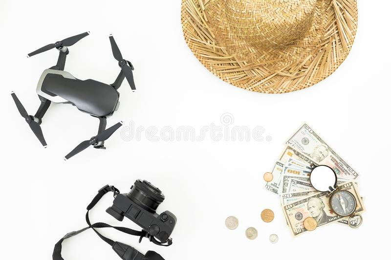Travel holiday concept with copy space. Drone, straw hat, camera, vintage compass and USA banknotes with coins on white background. Flat lay stock photography
