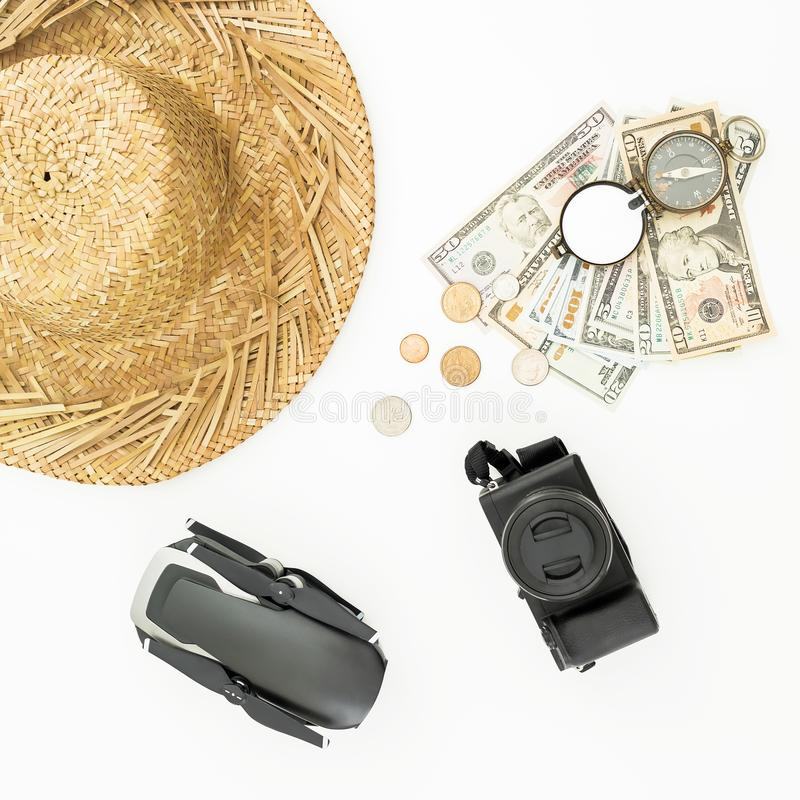 Travel holiday concept. Drone, straw hat, photo camera, compass and USA cash on white background. Flat lay, top view. royalty free stock photo