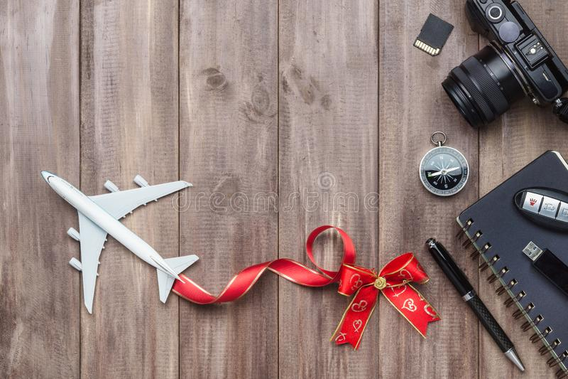 Travel holiday concept. White model of passenger plane with hear. T bows, camera, sd card, USB drive, compass and notebook on rusty wood background, top view royalty free stock image
