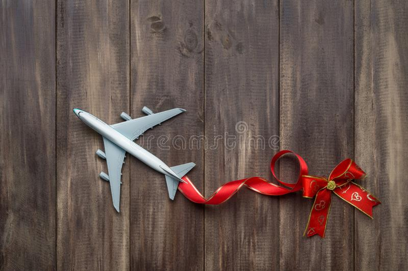Travel holiday concept. White model of passenger plane with hear. T bows on rusty wood background, top view with copy space. Special for travel holiday on New stock images