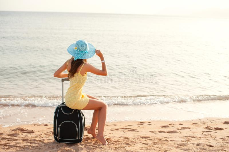 Travel holiday and people concept - woman tourist sitting near the sea on suitcase and in hat and watching sun and show thumbs up royalty free stock photos