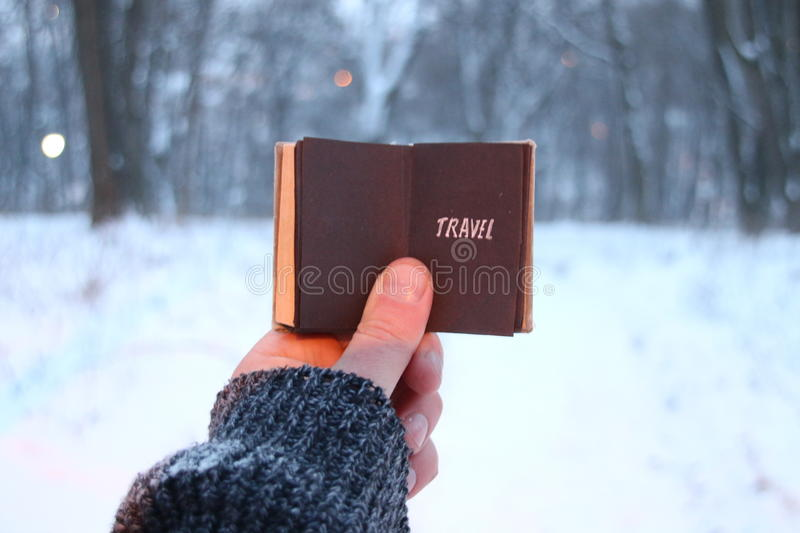 Travel idea, traveler holds a book in his hand with the inscription. Travel concept, traveler holds a book in his hand with the inscription on the background of royalty free stock photography