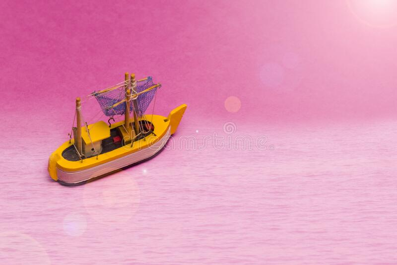 Travel Ideas and Concepts. Model of Old Sail Boat Placed Over Pink Background with Sunflares Added stock photography