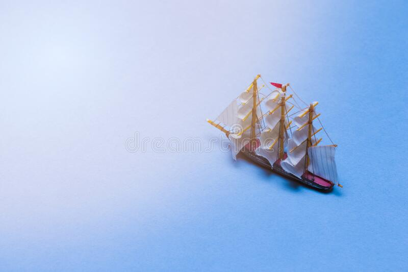 Travel Ideas and Concepts. Model of Three Masted Sailboat Placed Over Water Blue  Background with Added Suflares royalty free stock image