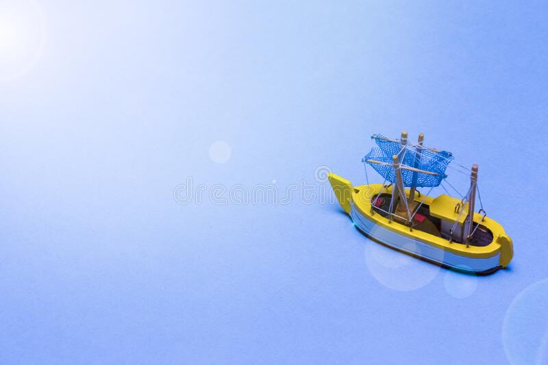 Travel Ideas and Concepts. Model of Wooden Old Sailboat Placed Over water Blue  Background with Added Suflares stock images