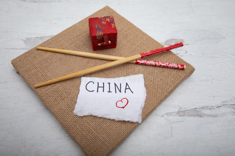 Travel industry background chopsticks oriental gift boxwhite piece of paper with the word China hand written on sign. Travel industry background chopsticks royalty free stock images