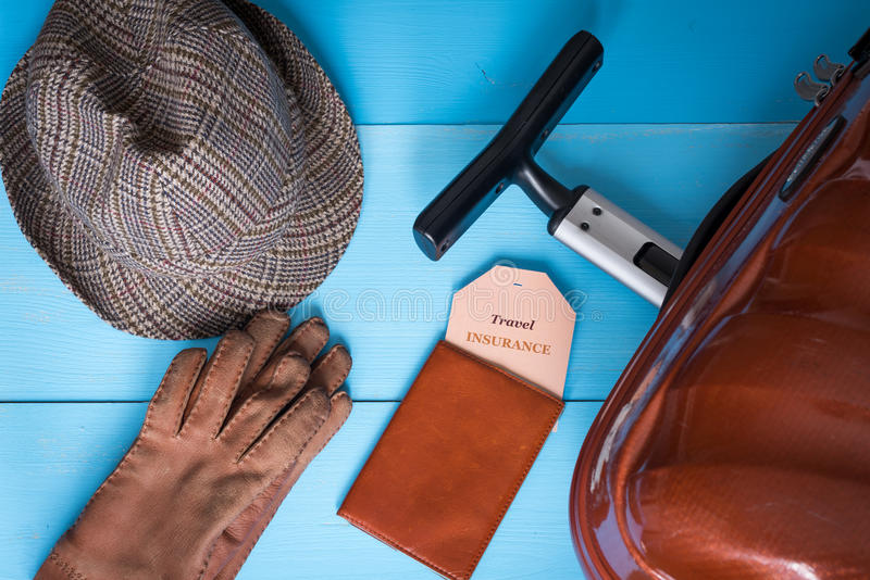 Travel insurance concept. Suitcase, hat, gloves, passport case, insurance tag. Insurance tag text is easily replaceable. Wooden background royalty free stock images