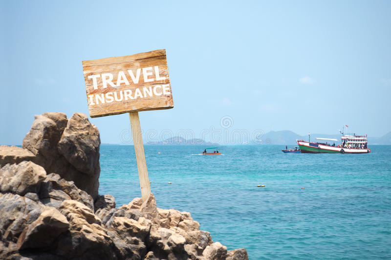 Travel insurance concept. Wooden billboard written word Travel insurance over passenger ships floating on the sea background stock photography