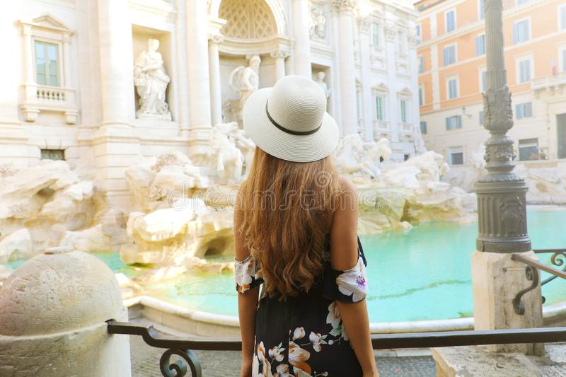 Travel in Italy. Back view of attractive woman looks Trevi fountain famous landmark in Rome. Happy girl enjoy Italian holiday in. Europe stock images