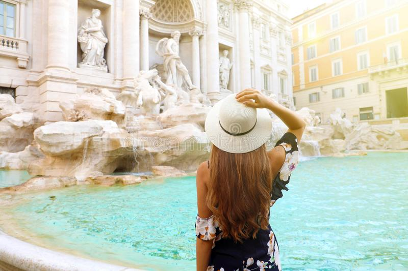 Travel in Italy. Back view attractive young woman looks Trevi fountain famous landmark in Rome. Happy girl enjoy Italian holiday royalty free stock photography