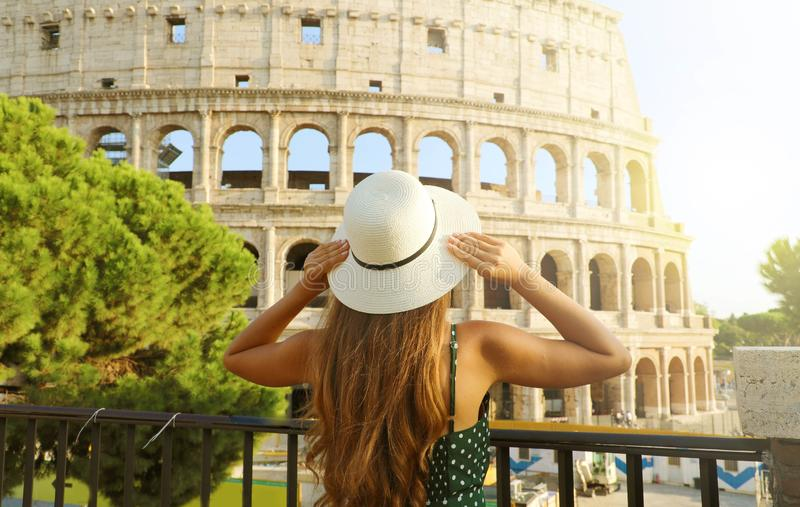 Travel in Italy. Back view of beautiful girl visiting Colosseum landmark at sunset in Rome. Summer holidays in Europe.  stock photos