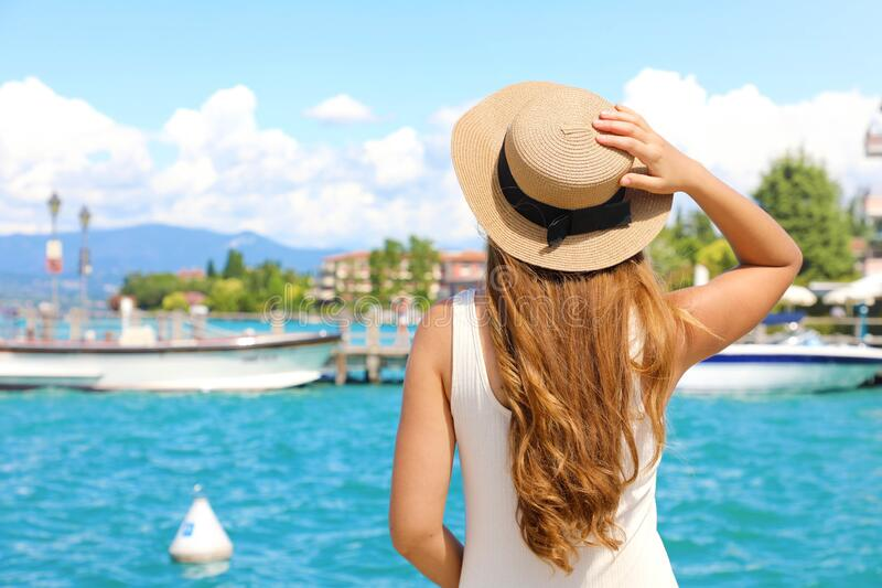 Travel in Italy. Back view of beautiful girl visiting Sirmione on Lake Garda. Summer holidays in Italy stock images