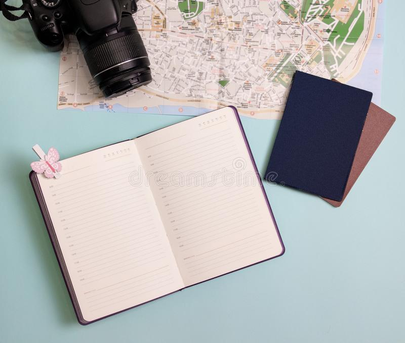 Travel items flatlay. On a blue background - a map, a camera, a notebook and a passport stock photography
