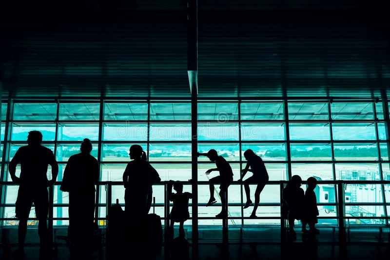Travel with Kids Concept. Silhouette of a Big Family Passengers Waiting for Boarding in Terminal Airport royalty free stock images