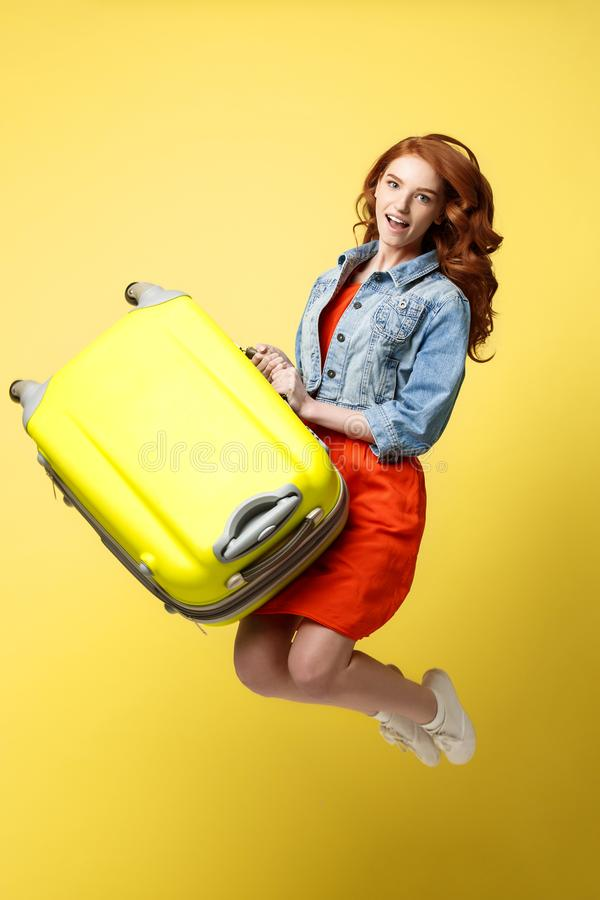 Travel and Lifestyle Concept: Portrait of a beautiful red hair fashion woman jumping and holding a bright green suitcase stock photos