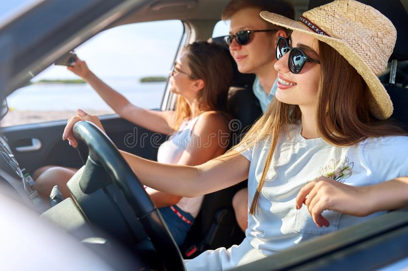 Friends rented a car for summer road trip to the beach. Female driver in glasses and straw hat having fun. Woman learned royalty free stock images