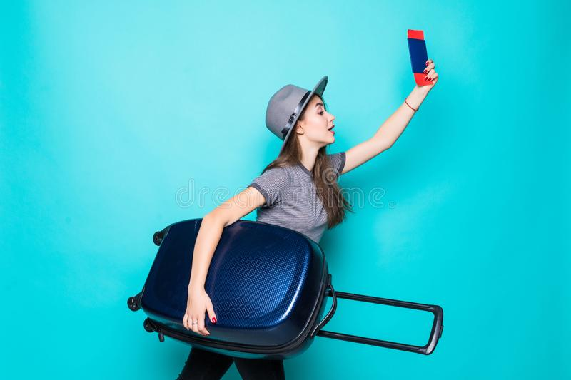 Travel and Lifestyle: Portrait of young woman holding passport with flying tickets standing with a suitcase over blue background. Portrait of young woman holding royalty free stock photo